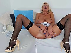 Busty old babe in fishnets plays with her cunt